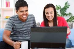 Pares cariñosos jovenes usando la computadora portátil en el país Fotos de archivo