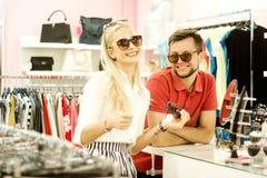 Pares cariñosos puestos en las gafas de sol El individuo y la muchacha en la tienda eligen los vidrios, accesorio Foto de archivo libre de regalías