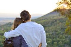 Pares cariñosos que abrazan al aire libre con la mirada en la puesta del sol roma Imágenes de archivo libres de regalías