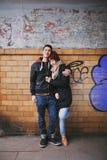 Pares cariñosos que abrazan contra una pared Imagen de archivo