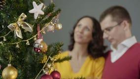 Pares cariñosos que admiran el feliz centelleo de las luces festivas que se colocan en abrazo almacen de metraje de vídeo