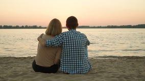 Pares cariñosos que admiran la puesta del sol almacen de metraje de vídeo