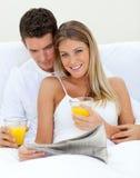 Pares cariñosos que beben el zumo de naranja Imagen de archivo