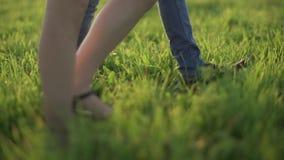 Pares cariñosos que caminan en campo Los pies se cierran para arriba en la hierba almacen de video