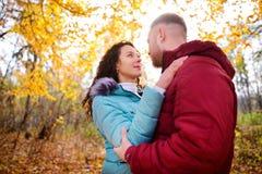 Pares cariñosos que caminan en el bosque y el abrazo del otoño Fotografía de archivo