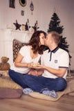 Pares cariñosos que celebran la Navidad y el Año Nuevo en casa que se sientan Imágenes de archivo libres de regalías