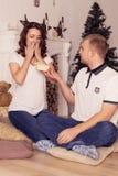 Pares cariñosos que celebran la Navidad y el Año Nuevo en casa que se sientan Imagen de archivo