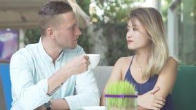 Pares cariñosos que charlan mientras que bebe el café Foto de archivo