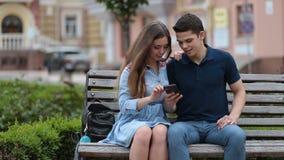 Pares cariñosos que comparten el medios contenido en smartphone metrajes