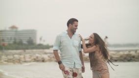 Pares cariñosos que corren a lo largo de la orilla de la playa y de besarse almacen de metraje de vídeo