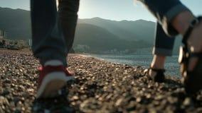 Pares cariñosos que dan un paseo a lo largo de la playa pedregosa el día soleado metrajes