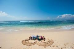 Pares cariñosos que descansan sobre la playa Fotos de archivo libres de regalías