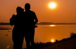 Pares cariñosos que disfrutan de la puesta del sol sobre el río fotografía de archivo