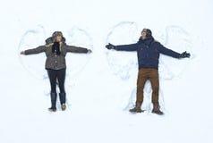Pares cariñosos que hacen ángel de la nieve Foto de archivo libre de regalías