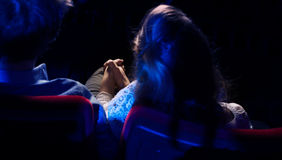 Pares cariñosos que llevan a cabo las manos en el cine Foto de archivo