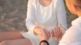 Pares cariñosos que llevan a cabo las manos que se sientan en la playa