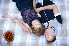 Pares cariñosos que mienten en la tela escocesa Fotografía de archivo libre de regalías