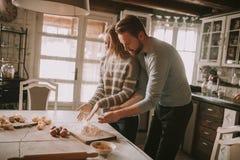 Pares cariñosos que preparan las pastas en la cocina Foto de archivo