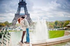 Pares cariñosos que se besan cerca de la torre Eiffel en par foto de archivo libre de regalías