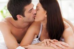 Pares cariñosos que se besan en cama. Foto de archivo libre de regalías