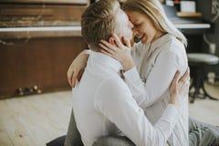 Pares cariñosos que se besan en el cuarto Imagenes de archivo