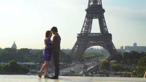 Pares cariñosos que se besan en fondo de la torre Eiffel metrajes