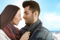 Pares cariñosos que se besan en la playa en el otoño Fotografía de archivo libre de regalías
