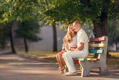 Pares cariñosos que se sientan en banch en parque Foto de archivo libre de regalías