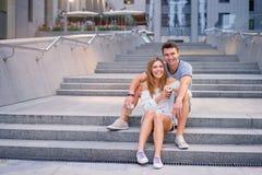 Pares cariñosos que se sientan en la escalera Imagen de archivo
