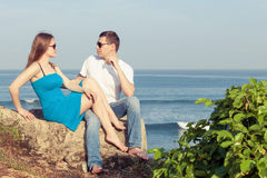 Pares cariñosos que se sientan en la playa en el tiempo del día Fotografía de archivo libre de regalías