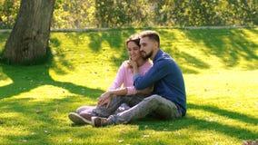 Pares cariñosos que se sientan en prado verde, abrazándose y disfrutando del momento almacen de video