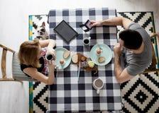 Pares cariñosos que se sientan en una tabla de cocina, desayunando junto Imágenes de archivo libres de regalías