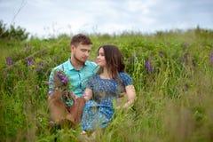 Pares cariñosos que se sientan junto en el medio de las flores en un prado honeymoon imagenes de archivo