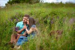 Pares cariñosos que se sientan junto en el medio de las flores en un prado honeymoon foto de archivo