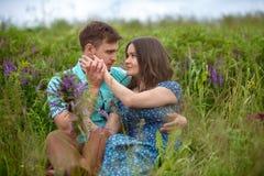 Pares cariñosos que se sientan junto en el medio de las flores en un prado honeymoon fotografía de archivo libre de regalías