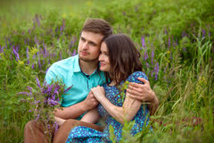 Pares cariñosos que se sientan junto en el medio de las flores en un prado honeymoon imágenes de archivo libres de regalías