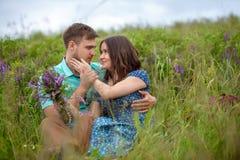Pares cariñosos que se sientan junto en el medio de las flores en un prado honeymoon foto de archivo libre de regalías