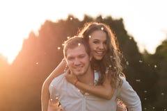 Pares cariñosos y felices en la puesta del sol Imagen de archivo libre de regalías
