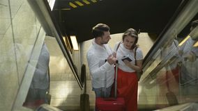 Pares cari?osos en la escalera m?vil en el aeropuerto Un individuo y su novia est?n viajando juntos Gente con el caucásico almacen de video