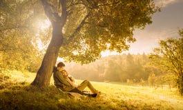 Pares cariñosos debajo de un árbol grande  Imagenes de archivo