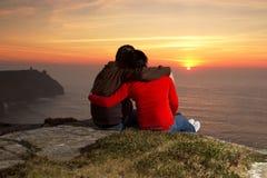 Pares cariñosos en la puesta del sol Imágenes de archivo libres de regalías
