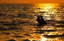 Pares cariñosos en la puesta del sol en el mar Fotografía de archivo libre de regalías