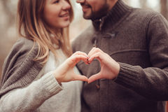 Pares cariñosos felices jovenes que muestran el corazón para el día de San Valentín en paseo al aire libre acogedor en bosque Imagenes de archivo