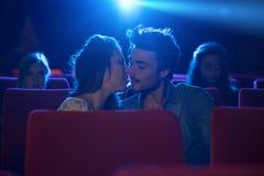 Pares cariñosos jovenes que se besan en el cine Foto de archivo