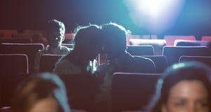 Pares cariñosos jovenes que se besan en el cine Fotografía de archivo