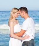 Pares cariñosos que abrazan en la playa Imagen de archivo