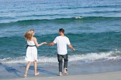 Pares cariñosos que recorren en la playa Foto de archivo