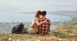 Pares cariñosos que se sientan en la colina sobre la ciudad Imagenes de archivo