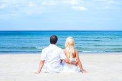 Pares cariñosos que se sientan y que abrazan en la playa Foto de archivo libre de regalías