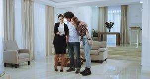 Pares carismáticos y agente inmobiliario que muestran la nueva casa y que usan una tableta para discutir el plan de la casa muy almacen de video